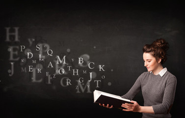 Young lady reading a book with alphabet letters