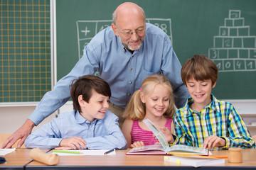 kinder in der schule blättern zusammen in einem buch