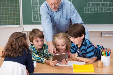 kinder und lehrer schauen auf tablet