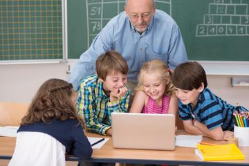 schüler und lehrer schauen auf einen laptop