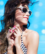 Young attractive happy brunette woman wearing sunglasses