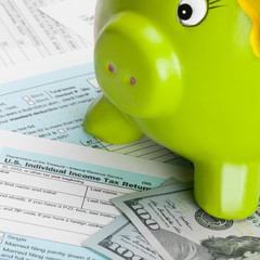 US Tax Form 1040 with piggy bank - 1 to 1 ratio