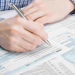 US Tax Form 1040 - man performing calculations - 1 to 1 ratio