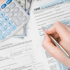 Man filling out 1040 US Tax Form - view from top - 1 to 1 ratio