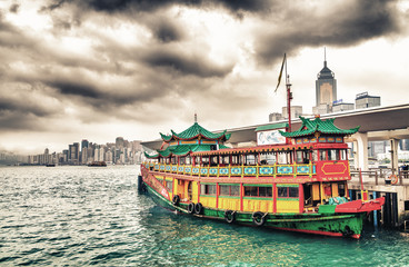 Hong Kong port. Colourful old cruise ship with city skyline on b