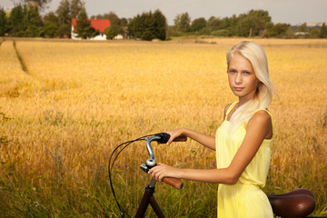 Young girl with a bike in the countryside.