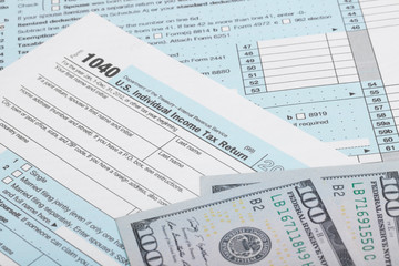 US 1040 Tax Form with two 100 US dollar bills over it