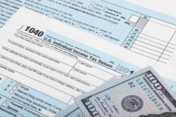 USA 1040 Tax Form with two 100 US dollar bills over it