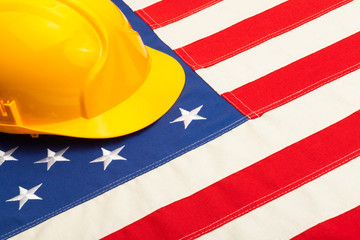 Yellow construction helmet laying over USA flag - studio shoot