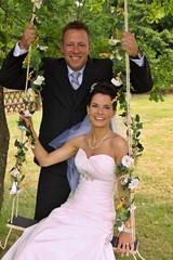 Groom swings the bride on a swing in outdoor park