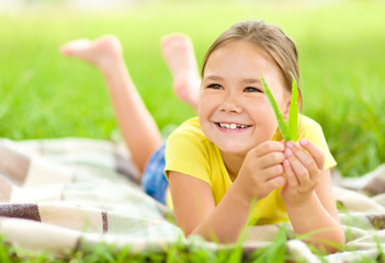 Portrait of a little girl laying on green grass