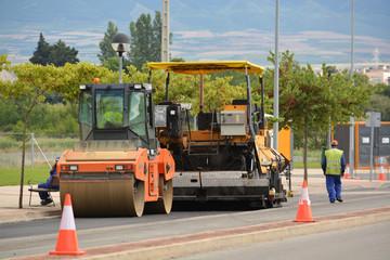 maquinas trabajando en el asfaltado de una calle