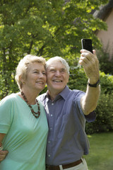 Elderly couple taking a selfie photo with a mobile phone