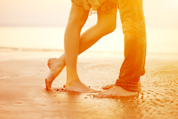 A loving young couple hugging and kissing on the beach at sunset