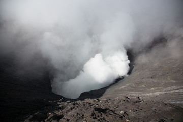 Active volcano crater with smoke