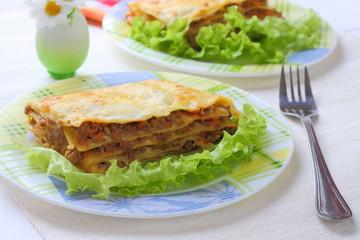 The traditional Italian national dish - beef lasagna with salad.