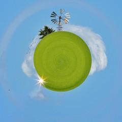 Astratto. Pianeta verde con mulino a vento