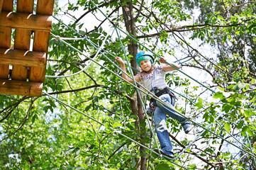 Girl is climbing to high rope bridge