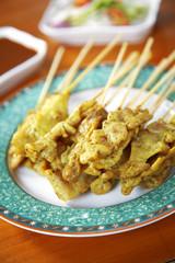 close up yellow indian pork satay in dish