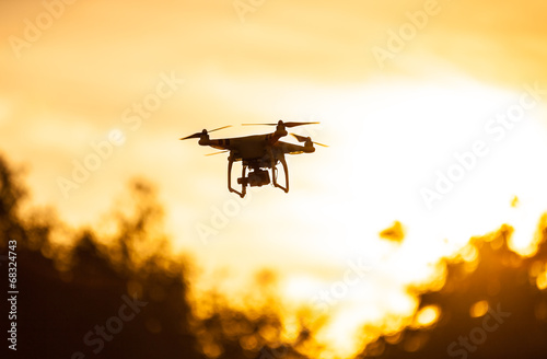 Leinwanddruck Bild Photo of a quadrocopter on sunset sky