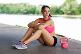 Woman sit with pink kettlebell