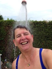 Frau unter der Gartendusche