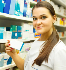 Pharmacist showing medicine box at pharmacy counter