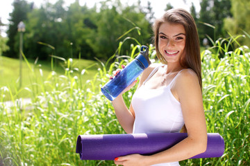Young woman with an exercise mat
