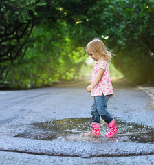 Cute little girl jumping into a puddle