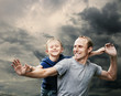 Happy laughing father with son with stormy sky background