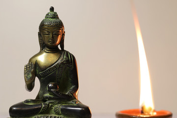 Statuette of Buddha and a burning candle.