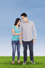 Attractive asian couple standing at field
