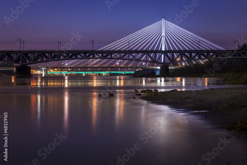 Backlit bridge at night and reflected in the water - 68329165