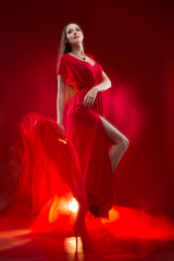 Beautiful woman in a red dress with pensive look