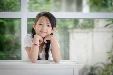 Little asian girl resting chin by hand