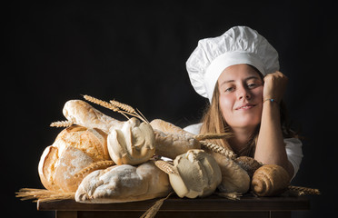 Young woman dressed as a baker near a table wiyh bread