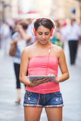 Beautiful Girl with Headphones and Digital Tablet in a Crowded S