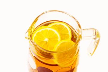 Cooling lemonade with lemon slices in a glass jug