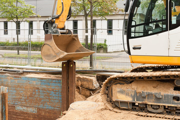 Eine Verbauplatte wird mit einem Bagger in den Boden gedrückt