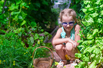 Cute little girl collects crop onions in the greenhouse
