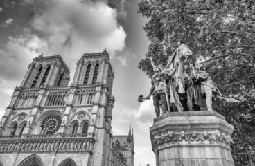 Notre Dame facade with statue and trees