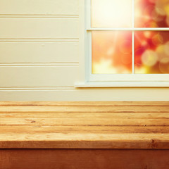 Empty wooden deck table with autumn window