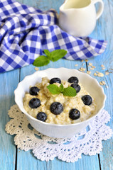 Oatmeal porridge with blueberry in a white bowl.