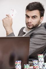 Poker player in a suit holding cards