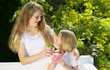 Sisters enjoying drinking lemonade outside on patio