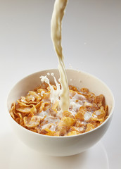 milk pouring into bowl with corn flakes