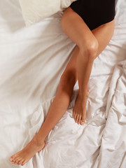 Sexy female legs on bed in bedroom