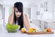 Woman hesitate to eat salad