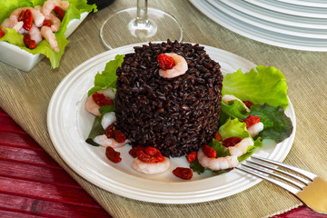 "Black rice called ""Venere rice"" on white plate with shrimps"