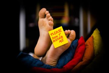 Feet on the sofa with a post card